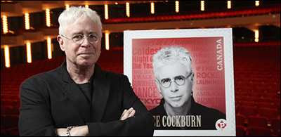 Bruce Cockburn poses with his forthcoming stamp, from True North Records